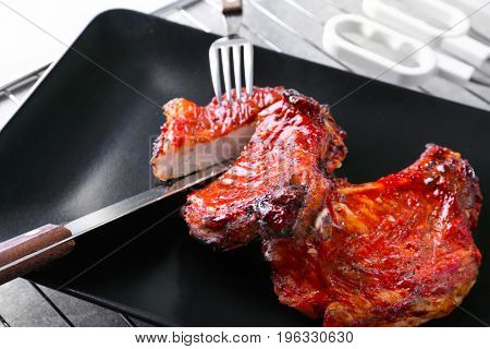 Plate with delicious pork ribs on kitchen table, closeup
