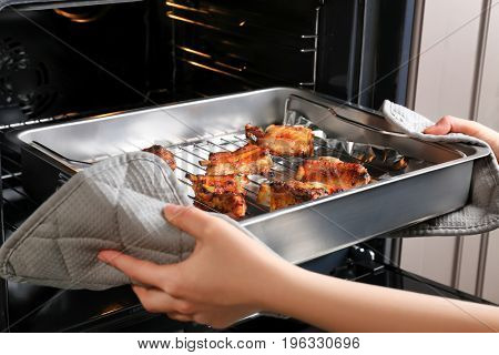 Young woman taking baking tray with delicious pork ribs out of oven