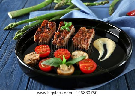 Black plate with delicious grilled sliced spare ribs with garnish on wooden table