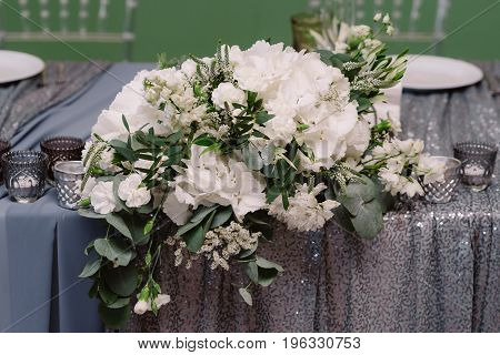 White floral decoration of the table on the silver cloth for the wedding ceremony