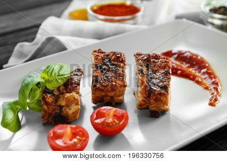 Delicious grilled spare ribs with cherry tomatoes and spicy sauce on white plate