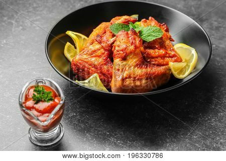 Delicious wings with sauce for chicken on kitchen table