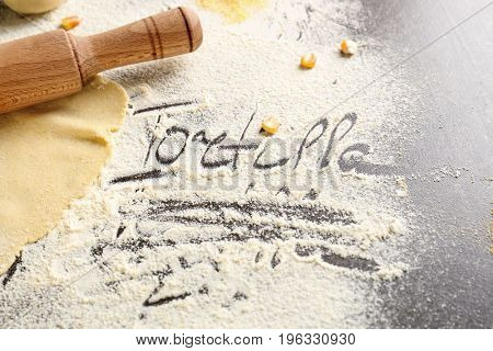 Word TORTILLA written on flour and raw dough with rolling pin, closeup