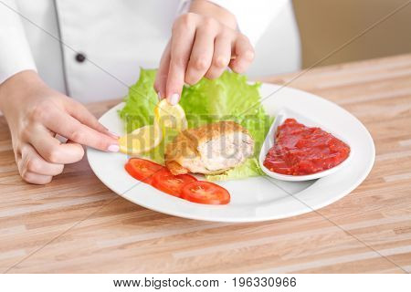 Female hands adding lemon slice to yummy fried chicken thigh with sauce on white plate