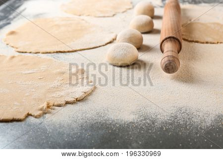 Unleavened dough for tortillas with rolling pin on kitchen table
