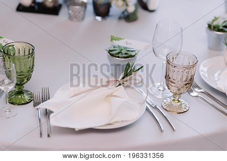 Wedding tableware, napkin with the tender ribbon on the plate and the silver pot with guest's name