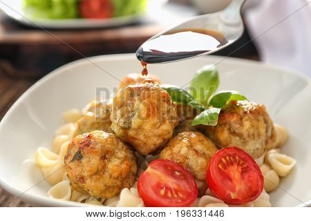 Pouring tasty sauce into bowl with turkey meatballs and pasta, closeup