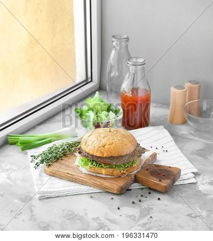 Composition with delicious homemade burger, tomato juice and vegetables on windowsill. Concept of food photography
