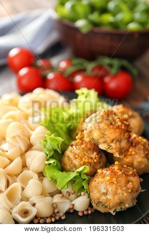 Plate with turkey meatballs and pasta on table, closeup