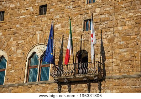 Close-up of flags on a balcony in front of the Palazzo Vecchio at sunset. In the city of Florence, the famous and amazing capital of the Italian Renaissance. Located in the Tuscany region