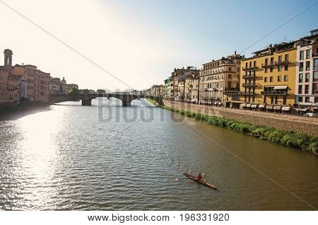 Overview of rower on the river Arno, bridge and buildings at sunset. In the city of Florence, the famous and amazing capital of the Italian Renaissance. Located in the Tuscany region