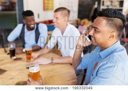 people, technology and communication concept - happy man calling on smartphone and drinking beer with friends at bar or pub
