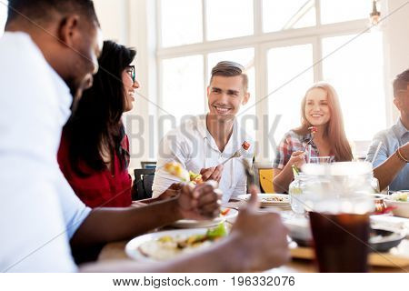 leisure, food and people concept - group of happy international friends eating and talking at restaurant table