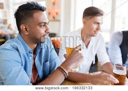 people, male friendship and communication concept - happy friends drinking beer at bar or pub