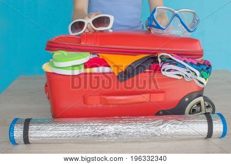 Woman hands putting clothes in suitcase closeup. Travel and vacations concept. Suitcase with different things prepared for travel