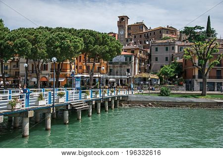 Passignano sul Trasimeno, Italy - May 15, 2013. View of the village and its harbor on the shores of Lake Trasimeno, a quiet and picturesque lake near Perugia. Located in Umbria region, central Italy