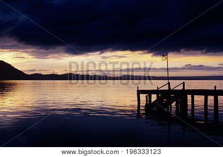 Silhouette of wooden wharf on a lake covered by dark storm clouds above during yellow sunset.