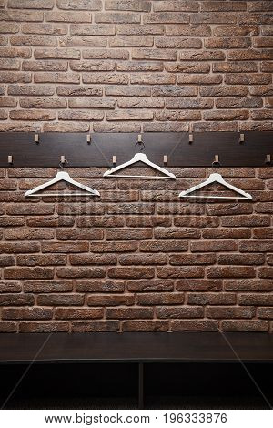 white hangers hanging without clothes on the brick wall