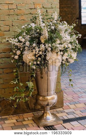 Floral vase near the brick wall for the wedding ceremony in the restaurant
