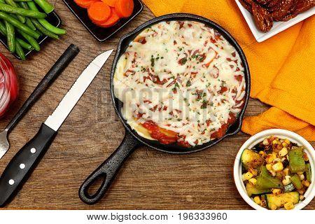 Skillet Baked Ravioli Meal with veggies and barley crisp at table.