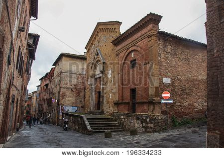 Siena, Italy - May 16, 2013. Street view and medieval buildings in a cloudy day at the town of Siena, famous for its horse race and parade called
