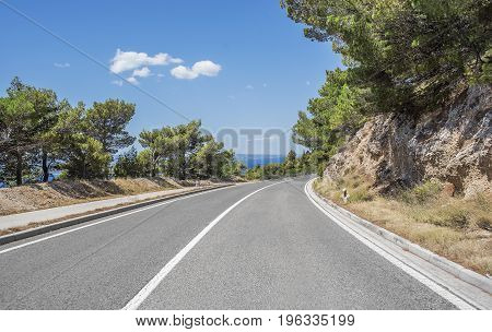 Country road for cars along the sea coast on a summer day.