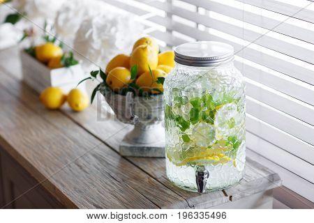 Jar of tasty fresh lemonade with ice and mint. Lemons on background. Style lemon. Wedding decor