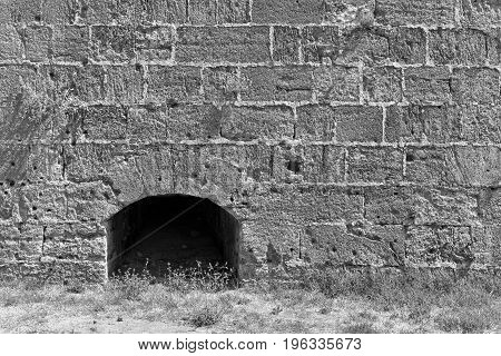 big stone wall of ancient fortress with a niche monochrome tone