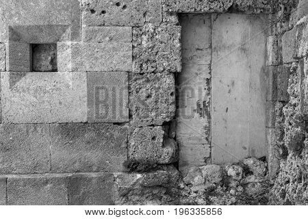 very old door on an ancient stone wall of monochrome tone