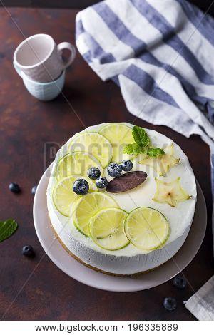 Lemon yogurt mousse cake, mojito berry cake on a plate on a brown stone background flat lay