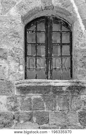 old window closeup on an ancient stone wall monochrome tone