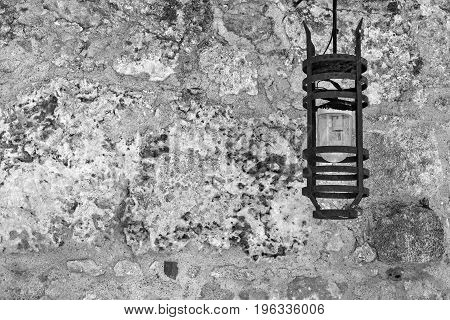 one steel lamp on an ancient stone wall of monochrome color
