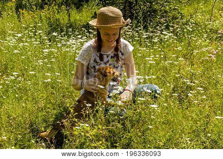 Smiling young girl with hair braids and hat with her pet dog in a field