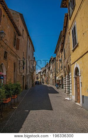 Orvieto, Italy - May 17, 2013. Overview of an alley with old buildings and shop on a sunny day, at the town of Orvieto, a pleasant and well preserved medieval city. Located in Umbria, central Italy