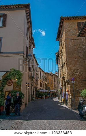 Orvieto, Italy - May 17, 2013. Overview of an alley with old buildings and people on a sunny day, at the town of Orvieto, a pleasant and well preserved medieval city. Located in Umbria, central Italy
