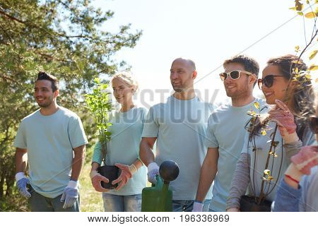 volunteering, charity, people and ecology concept - group of happy volunteers with tree seedlings and watering can in park