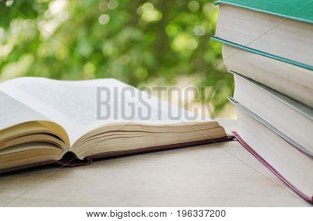 Open book and stack of books on the background of a window with greens.