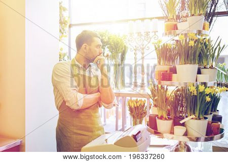 people, sale, retail, business and floristry concept - sad florist man with cashbox standing at flower shop counter