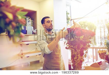 people, business, sale and floristry concept - happy smiling florist man with red roses at flower shop