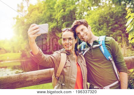 travel, hiking, backpacking, tourism and people concept - smiling couple with backpacks taking selfie by smartphone in nature