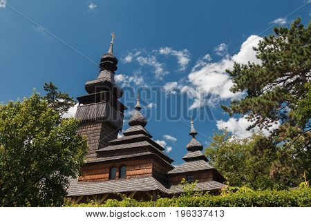 Old wooden Lemk church against a bright blue sky with clouds. Culture of Ukraine