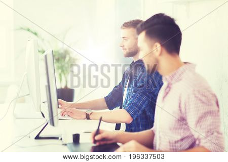 business, technology, education and people concept - young creative man or designer with computer at office