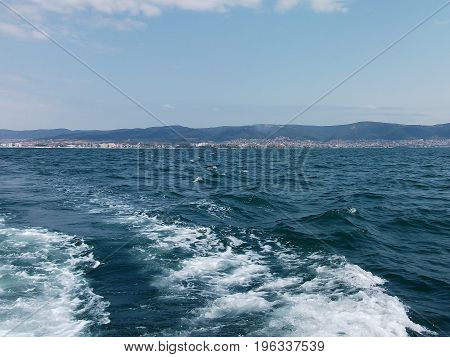 Black Sea Surface Summer Wave Background. View From Yacht. Exotic Seascape With Clouds And Town On H