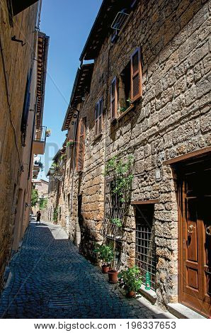 Orvieto, Italy - May 17, 2013. Overview of an alley with old buildings and wooden door under a sunny blue sky, at the town of Orvieto, a pleasant and well preserved medieval city. Located in Umbria