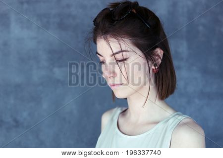 Beautiful sad girl lowered her eyes, portrait in profile, blue background