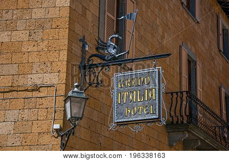 Orvieto, Italy - May 17, 2013. Close-up of elaborate Hotel plate, made of iron, stuck in stone wall and lamp in Orvieto, a pleasant and well preserved medieval town. Located in Umbria, central Italy