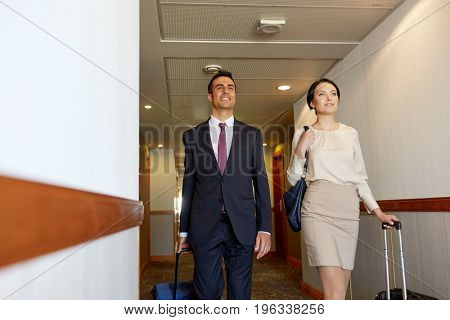 business trip and people concept - man and woman with travel bags at hotel corridor