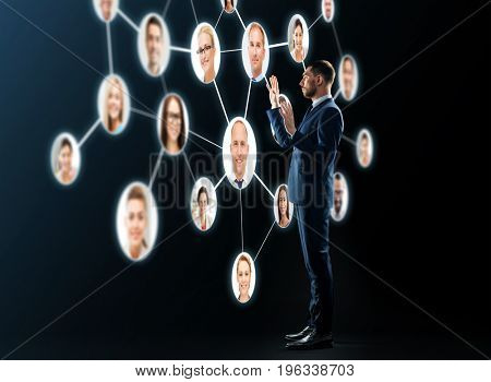business, people, corporate, headhunting and technology concept - buisnessman in suit looking at contacts network over black background