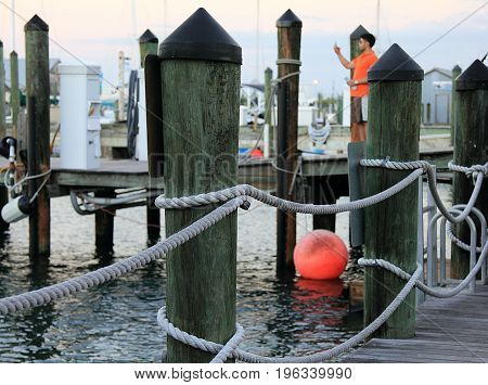 KEY WEST, FLORIDA - NOVEMBER 30, 2013: A pier in Key West, Florida with an orange buoy and a guy in orange shirt on background