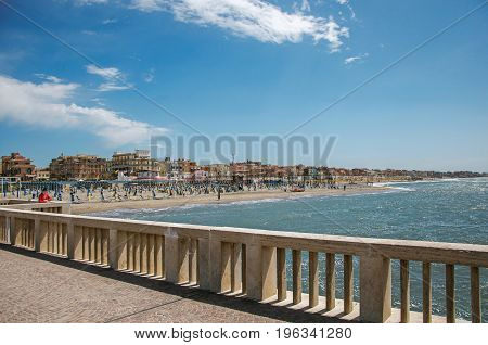 Ostia, Italy - May 18, 2013. View of marble pier, with the beach and the city of Ostia in the background, on a sunny day. The town is a seaside resort and ancient port of Rome. Lazio region